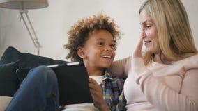 Mamma della donna con suo figlio che si siede sul sofà e che esamina compressa stock footage
