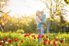 Mamma della famiglia con la donna della figlia con il bambino nel supporto di primavera e la HU immagine stock