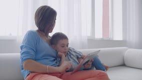 Mamma della famiglia e figlio felici facendo uso della compressa digitale che si siede sul sofà, madre sorridente del bambino del stock footage