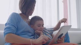 Mamma della famiglia e figlio felici facendo uso della compressa digitale che si siede sul sofà, madre sorridente del bambino del archivi video