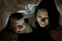 Mamma della giovane donna ed il suo film interessante di sorveglianza del figlio insieme sulla compressa e sulla risata sotto la  Immagini Stock Libere da Diritti