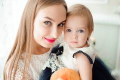 Mamma die en zijn kleine dochter koesteren kussen royalty-vrije stock afbeelding