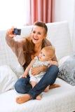 Mamma, die Fotos mit ihrem reizenden Schätzchen bildet Stockfoto