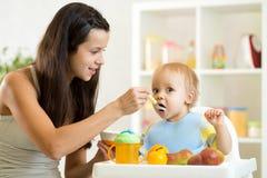 Mamma die gehomogeniseerd voedsel geven aan haar babyzoon op hoge stoel in keuken stock foto's