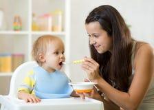 Mamma die gehomogeniseerd voedsel geven aan haar babyzoon op hoge stoel in keuken royalty-vrije stock afbeelding