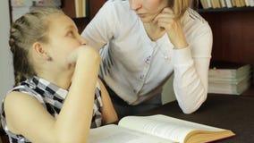 Mamma die haar daughter do homework helpen het schoolmeisje maakt lessen stock footage