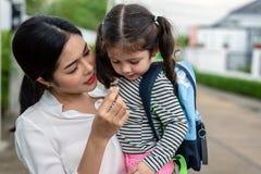 Mamma die haar dochter met snack voeden alvorens naar school te gaan Terug naar school en onderwijsconcept Huis zoet huis en gelu royalty-vrije stock afbeeldingen