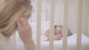 Mamma die op slaapkind kijken in wieg stock footage