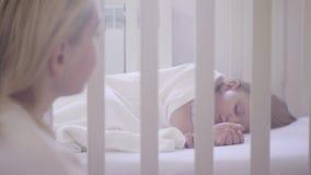 Mamma die op slaapkind kijken in wieg stock videobeelden
