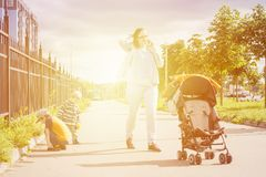 Mamma die telefonisch tijdens openluchtgang met jonge geitjes spreken Royalty-vrije Stock Fotografie