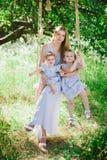 Mamma die twee dochters in openlucht koesteren Stock Afbeeldingen