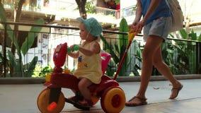 Mamma die weinig dochter berijden op de fiets van kinderen terwijl het lopen op de zomervakantie stock footage