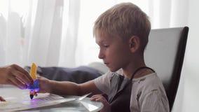 Mamma die zijn zoon helpen om zijn thuiswerk te doen stock videobeelden