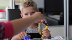 Mamma die zijn zoon helpen om zijn thuiswerk te doen stock footage