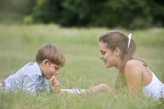 Mamma die zoon met thuiswerk helpen, die op gras bepalen stock afbeeldingen