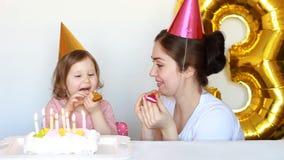 Mamma e bambino e torta di compleanno felici al partito Generi i suoi sorrisi e laughes della figlia su un fondo bianco 3 anni archivi video