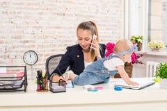 Mamma e donna di affari che lavorano con il computer portatile nel paese e che giocano con la sua neonata fotografie stock libere da diritti