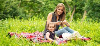 Mamma e fare da baby-sitter su una coperta del plaid immagini stock