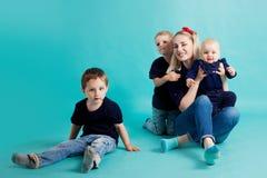 Mamma e figli, ritratto su fondo blu immagini stock libere da diritti
