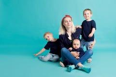 Mamma e figli, ritratto su fondo blu fotografie stock