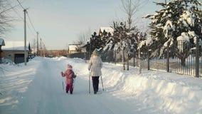 Mamma e figlia che fanno nordico che cammina nella periferia nell'inverno video d archivio