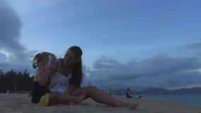 Mamma e figlia che giocano con la sabbia sulla spiaggia Stanno ridendo Piedi della sabbia della mamma e solleticare sua figlia archivi video