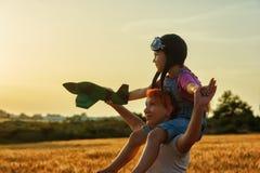 Mamma e figlia che giocano nel campo al tramonto con un aeromodellino fotografia stock libera da diritti