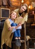 Mamma e figlia che leggono insieme Donna avvolta in libro generale di lana della tenuta Madre che aiuta adolescente con Fotografia Stock Libera da Diritti