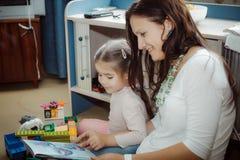 Mamma e figlia che leggono un libro molto interessante considerato fotografie stock