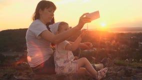 Mamma e figlia che per mezzo del telefono che si siede su una collina al tramonto su una sera di estate archivi video