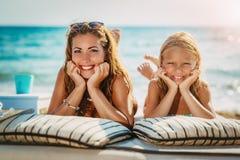 Mamma e figlia che posano alla spiaggia immagini stock libere da diritti