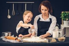 Mamma e figlia che preparano gli gnocchi nella cucina immagine stock
