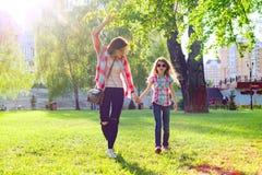 Mamma e figlia che si tengono per mano camminata nel parco fotografia stock
