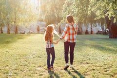 Mamma e figlia che si tengono per mano camminata nel parco, ora dorata, vista posteriore immagine stock