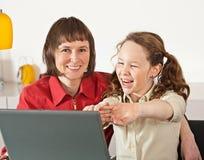 Mamma e figlia con il computer portatile Fotografia Stock