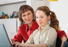 Mamma e figlia con il computer portatile Immagini Stock