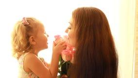 Mamma e figlia con un mazzo delle rose dei fiori Il concetto di un giorno o di un compleanno del ` s della madre archivi video