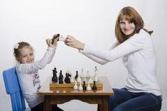 Mamma e figlia divertendosi giocando scacchi immagini stock libere da diritti