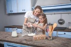 Mamma e figlia nel cuoco Mafins della cucina la figlia rompe l'uovo sopra la farina fotografie stock
