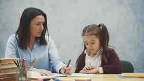 Mamma e figlia su un fondo grigio Durante il questo, scrive il compito per una figlia sorridente Concetto delle relazioni stock footage