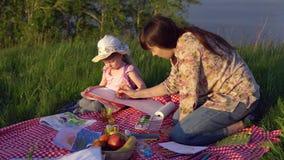 Mamma e figlia su un picnic su una collina vicino allo stagno stock footage