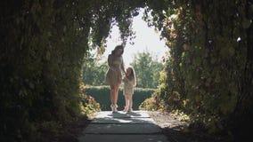 Mamma e figlia in un tunnel dei cespugli stock footage