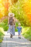 Mamma e figlio che camminano lungo la strada nel parco Vista posteriore fotografie stock