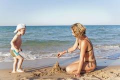 Mamma e figlio che costruiscono un castello della sabbia Fotografie Stock