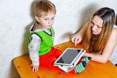 Mamma e figlio che giocano con il PC della compressa immagine stock libera da diritti