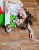 Mamma e figlio che giocano con il pc della compressa mentre trovandosi sul pavimento immagine stock libera da diritti