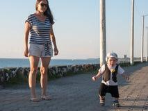 Mamma e figlio che giocano vicino all'oceano al tramonto In un'espressione facciale divertente del bambino molto bello Immagine Stock