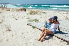 Mamma e figlio che si rilassano e che abbracciano sulla spiaggia Fotografie Stock