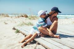 Mamma e figlio che si rilassano e che abbracciano sulla spiaggia Immagine Stock Libera da Diritti