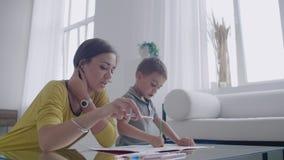 Mamma e figlio che si siedono alla tavola dello specchio nel tiraggio della stanza bianca con le matite colorate che sorridono e  stock footage